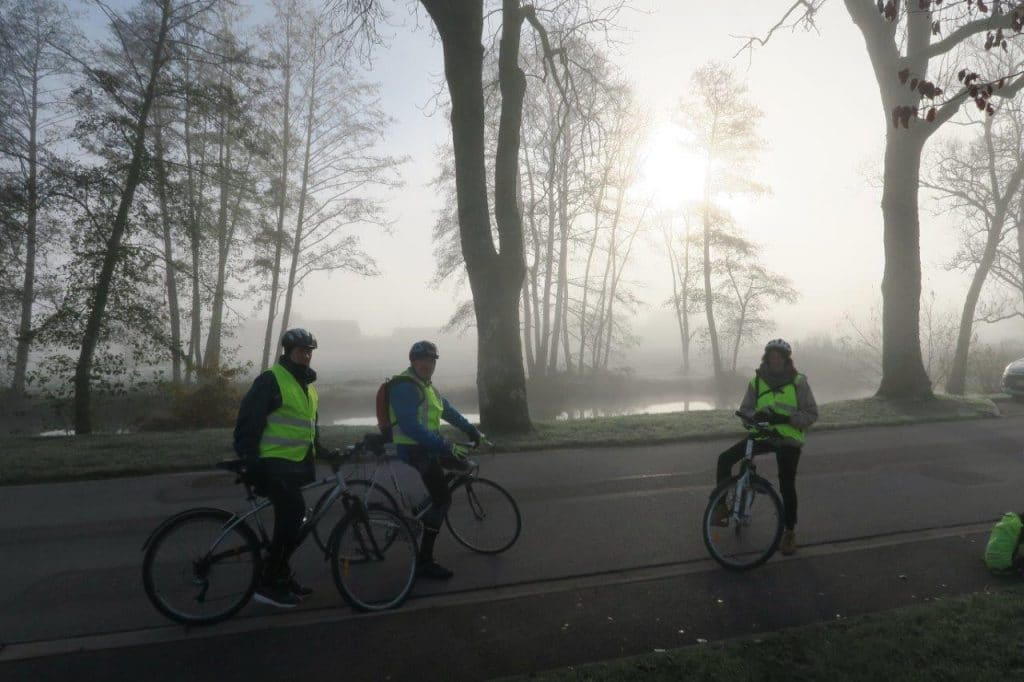 Photo de 3 cyclistes sur fond de brume matinale