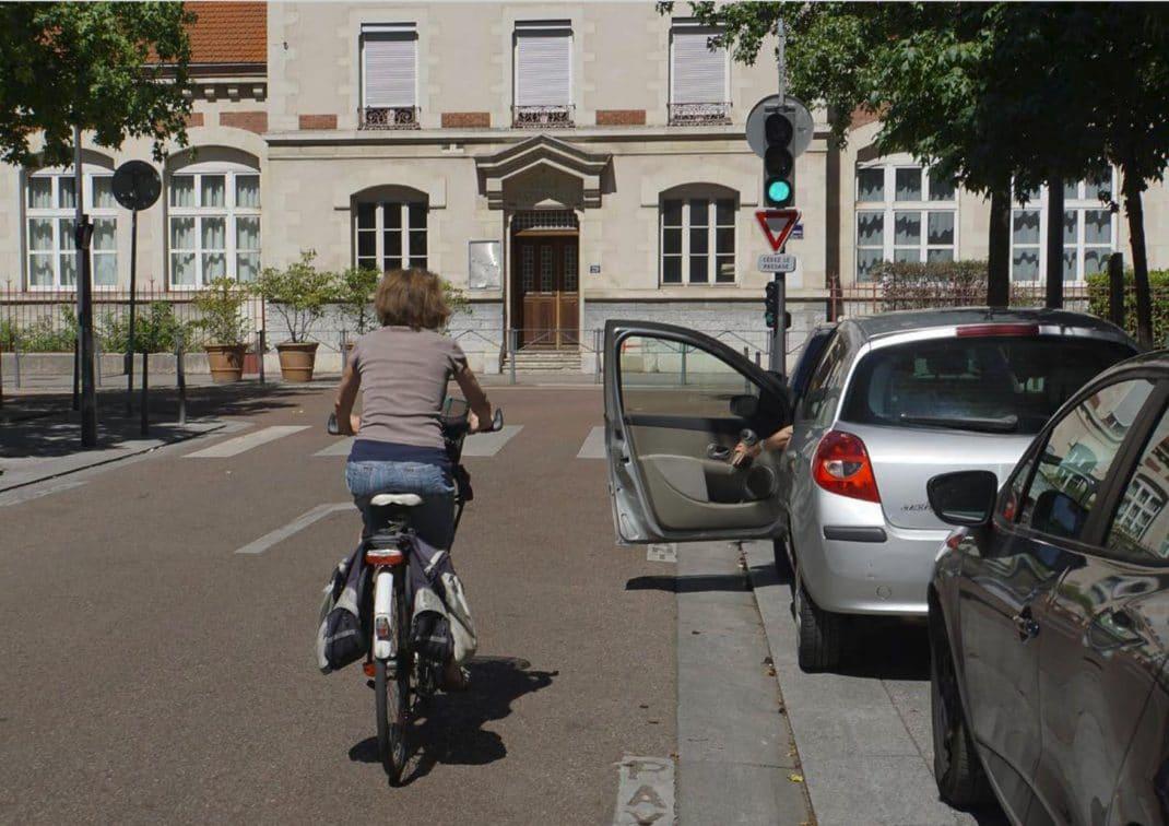 Cycliste se déportant pour éviter une portière de voiture en stationnement qui s'ouvre