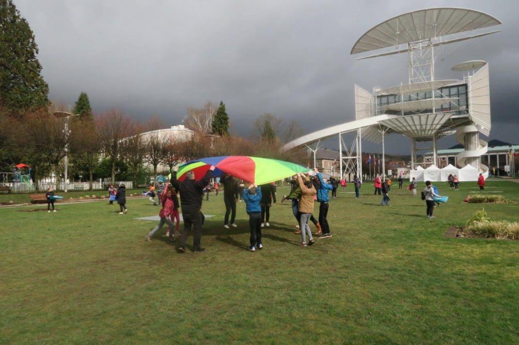 Elèves sur la pelouse au pied de la Tour de la Liberté avec parachute et coxi bola