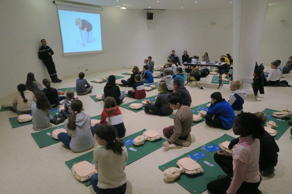 Groupe d'élèves apprenant le massage cardiaque