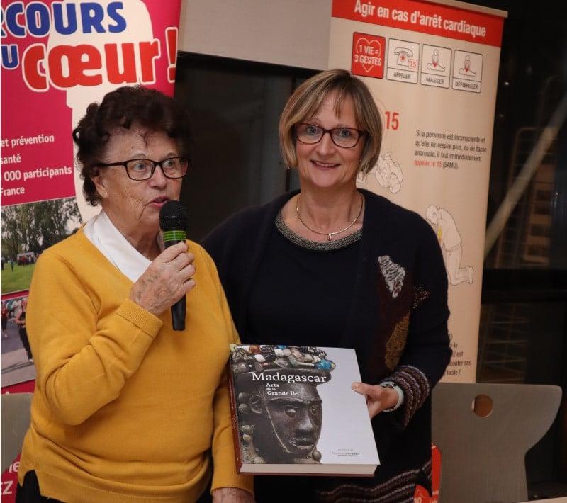 Annie Thrion reçoit des mains de Guilaine Bedel un livre sur l'exposition sur Madagascar qui se tient au Musée du quai Branly à Paris