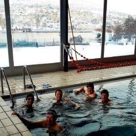 Photos des nageurs dans la piscine avec la vue sur la ville de Gérardmer enneigée au travers es baies vitrées